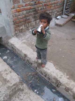A little boy drinks from a cup of water in the street outside his home, Agra India.